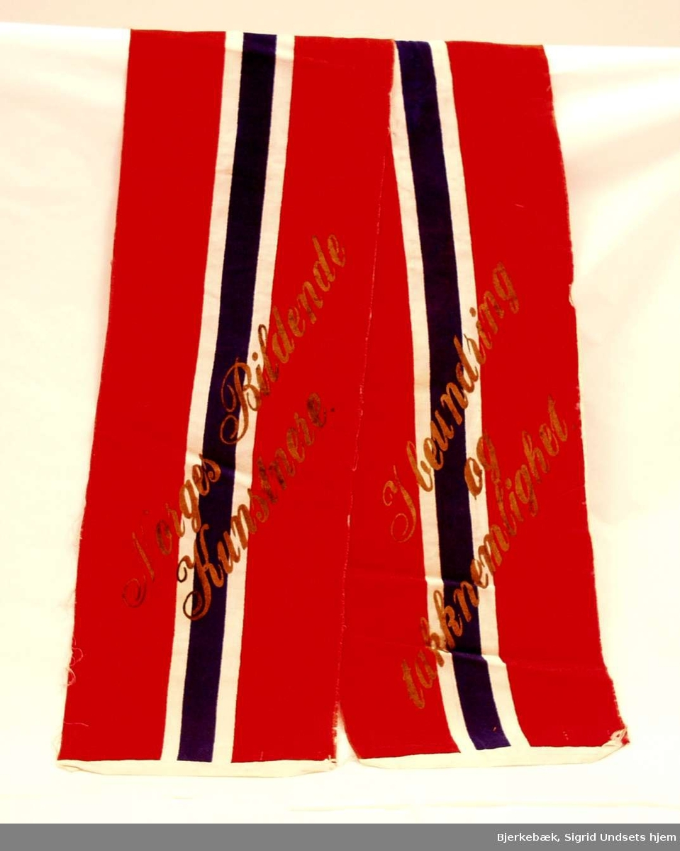 Bånd i rød, hvit og blå silke; flaggremse. Båndet er i to deler. På det ene står det: I beundring og takknemlighet. På det andre: Norges bildede kunstnere.
