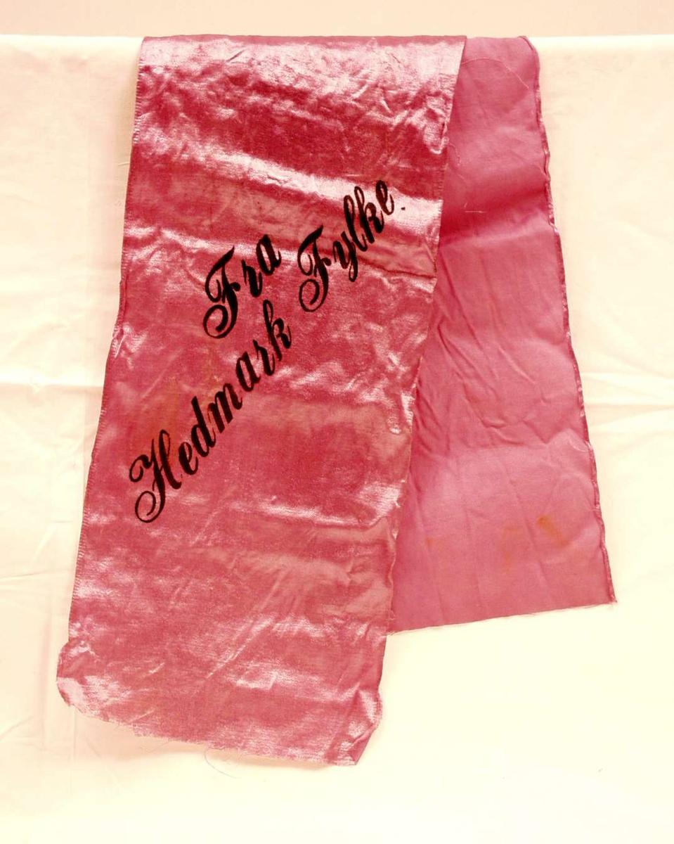 Bånd i lilla silke. På sløyfen står det skrevet: Fra Hedmark fylke.
