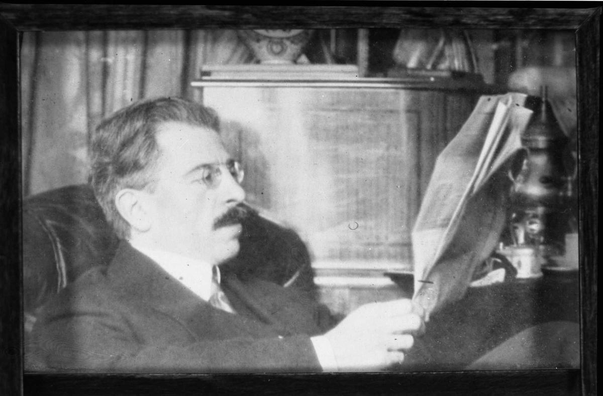 Mann i hjemlig miljø, leser avisen.