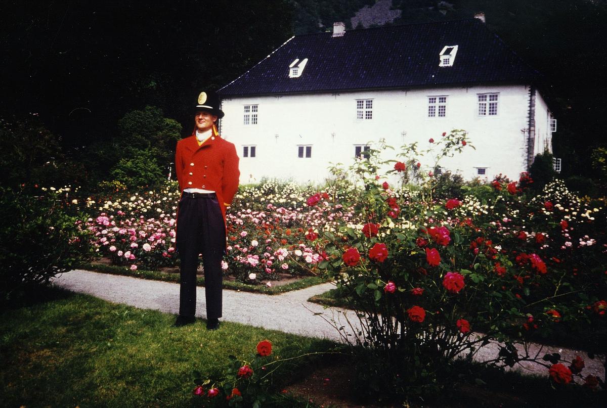 uniformer, mann i gammel dansk postuniform utenfor Rosendal Baroni, roser i bedene