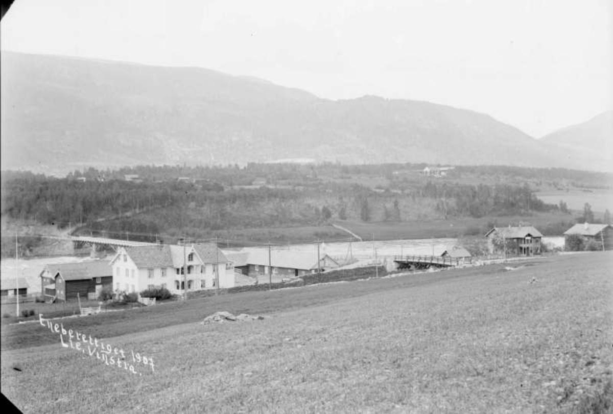 12.06.1907. N. Byhre, Sundbroen og Præstegaarden. Boliger, uthus, elv, bro, åsside med trær, dyrket mark.