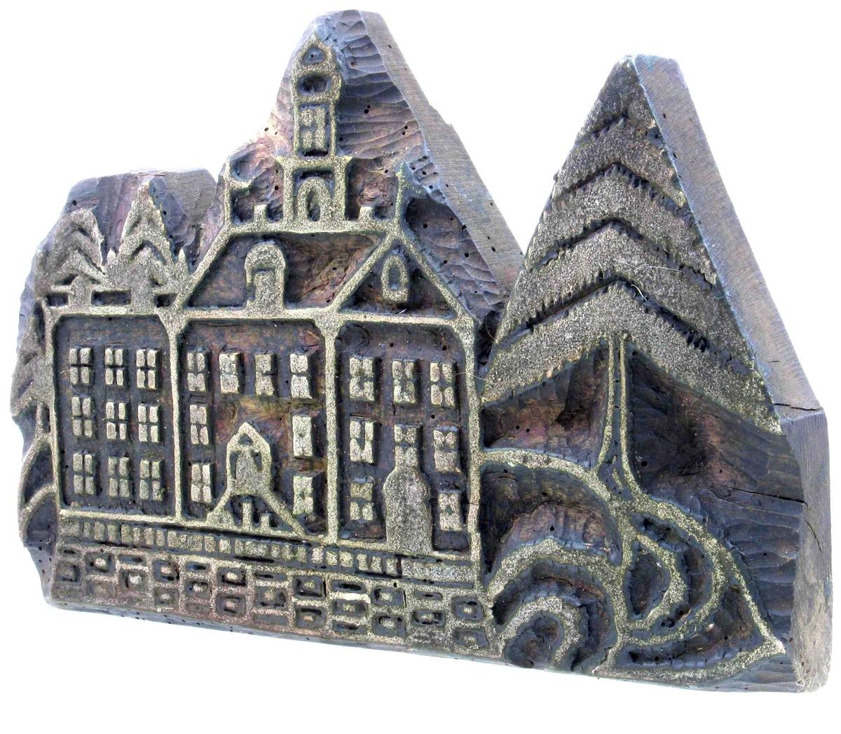 Slott med valmtak, fløyer og tårn,  tre etasjer, med portal med trapp, på terrasse,  omgitt av grantrær. Dansk 1700 tallsarkitektur.   Naiv utformning,