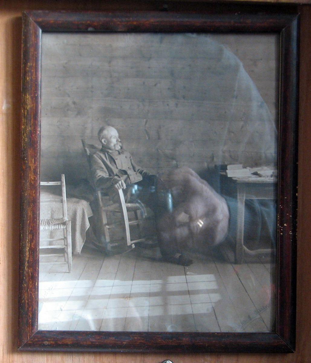 Rektangulært. A. Garborg sittende i gyngestol; høyrev.; snipp av divan og stol.