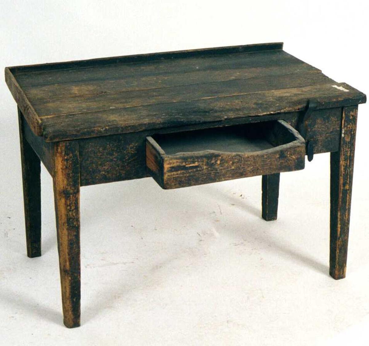 Skomakerbord .  Furu,  sort malt.   Rektangulært  bord med rette ben, bordplate av  fire planker på langs, den fremste svært slitt  i forkant. Karm på to sider, karmen borte på den ene kortside. I forkant th. en rem, midt  i sargen en skuff, sterkt avslitt i kanten øverst  Bordplatens bord er løse.