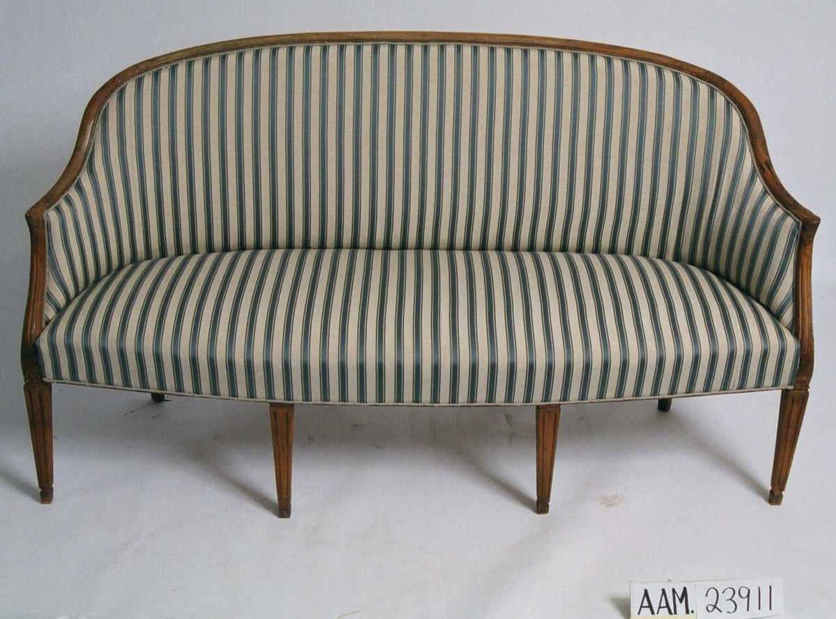 Sofa, empire.  Bjerk, stripet  bolstertrekk, strie. Rett rygg, svakt svungne lener som er i samme høyde som ryggen. Svungne flate ben som har smal rektangulær grunnflate. Stripet bolstertrekk, lysgrå bunnfarge med blå striper og smale rød/gule/blå striper. P. baksiden av ryggen strie, dekker med et eldre bolstertrekk med mørk grå bunnfarge og striper i gult/rødt. Tilstand: markstukken.