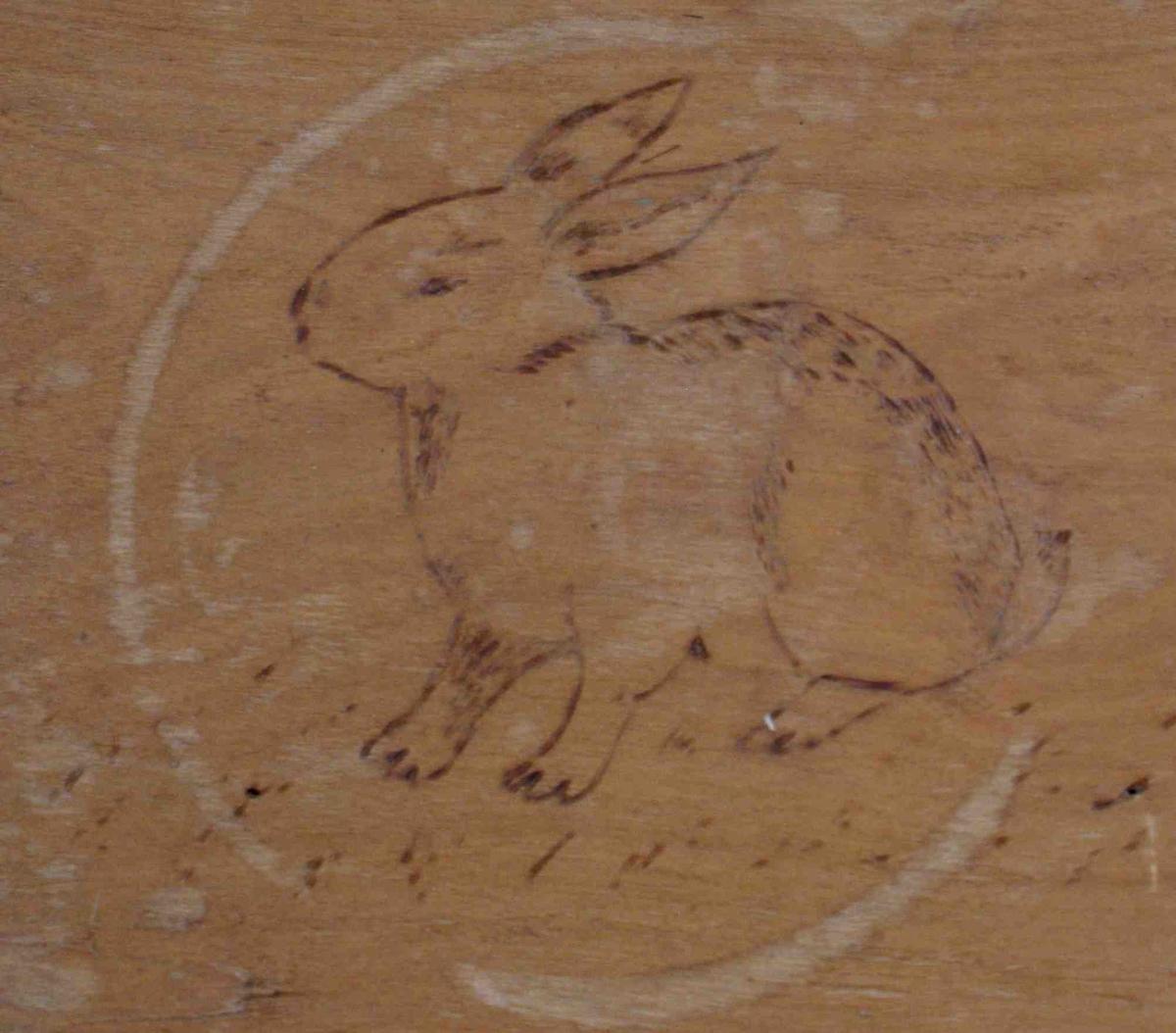 Bilde av en kanin, svidd inn i bunnen av trauet. Enkelt vegetabilsk motiv på handtakene i trauets kortsider.