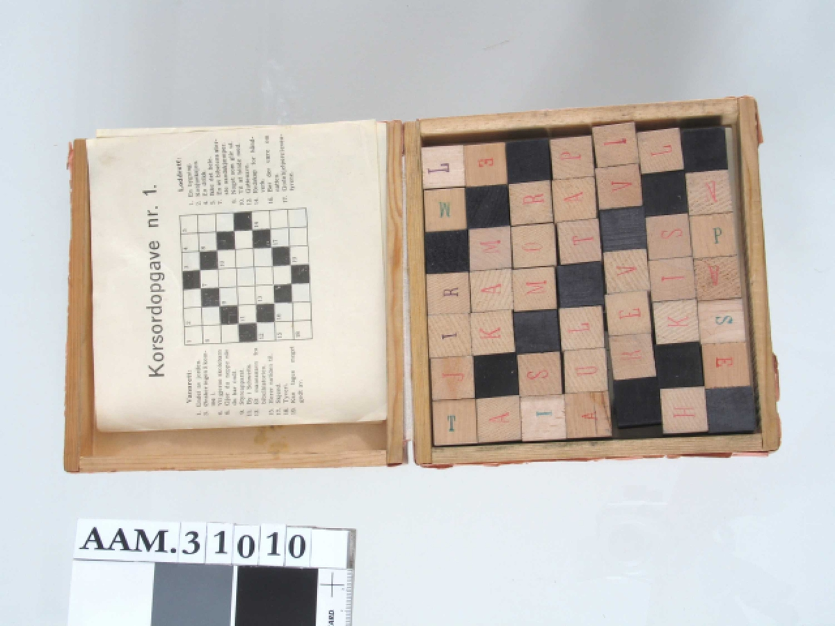 Kvadratisk eske med 49 små klosser, sorte eller med bokstaver p alle sider.