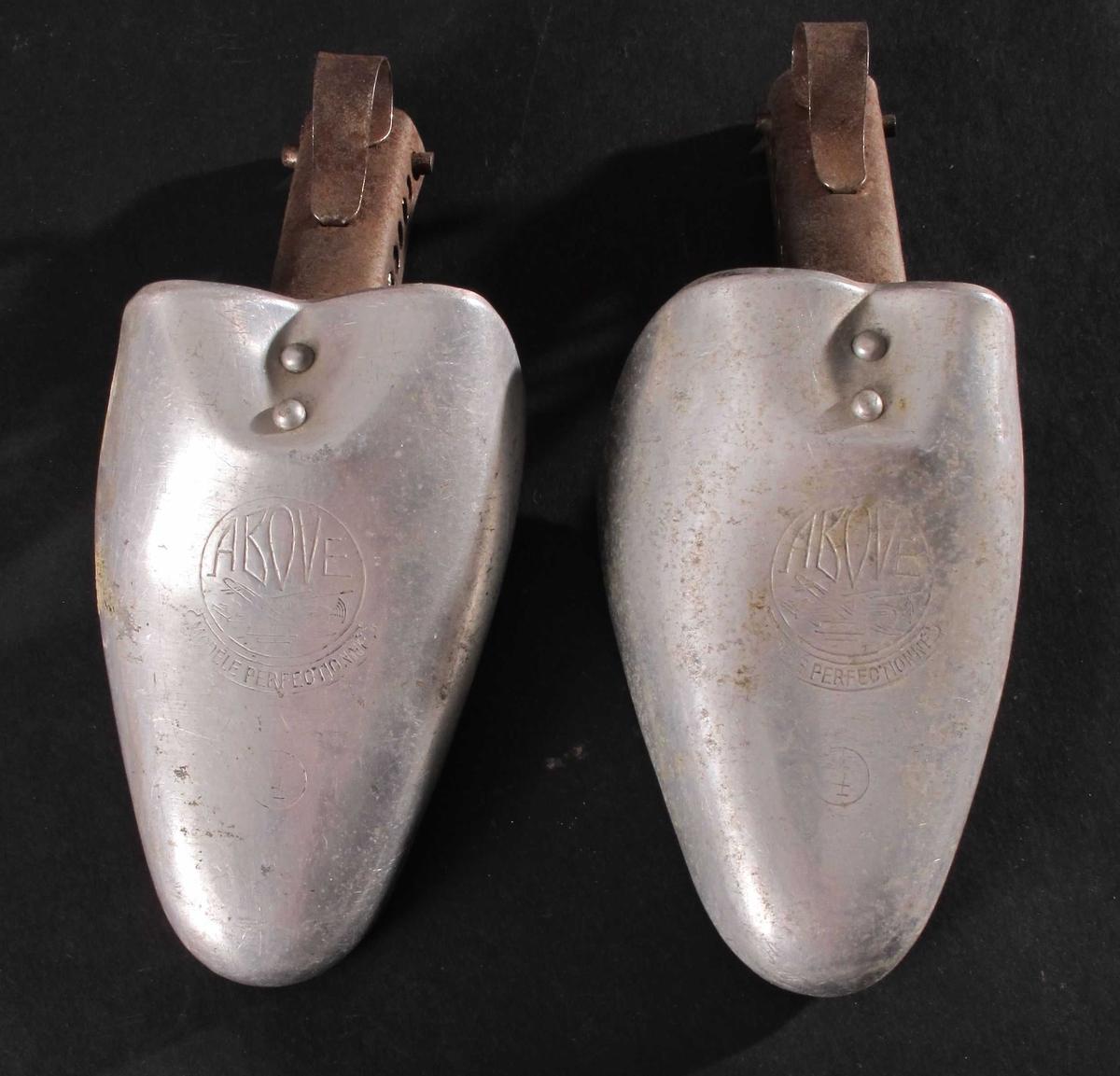 Skoformere i aluminium.  Til damesko.  Tåkappe i skoform, med en hengslet del i jern for å spenne mot hælen.  Hengslet rett under tåkappa, og omtrent midt på   Oppå tåkappa er det stemplet inn merke på begge.  Høyre tåkappe har et rundt klistremerke på innsidea med 530143 skrevet med blyant og 245- stemplet