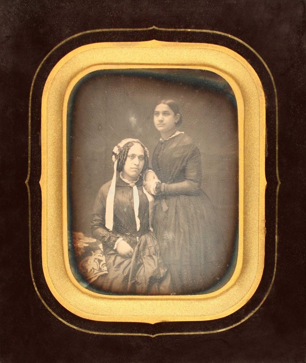 Portrett av to søstre, Hedevig Berg og Bella Nan, 1851. To kvinner, sittende/stående,  sittende kvinne med hengekrøller og hvitt hodeplagg med  lange bånd nedover kjolen. Brosje i halsen og rysj i forkant,  v. albu hviler mot bordkant. Th. stående kvinne, venstrevendt,  hviler begge hender mot den annens skulder.  Sort innramning med gull innerst.