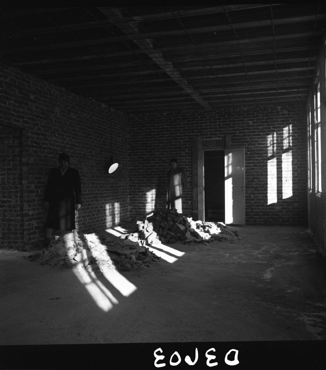 Aust-Agder-Museets første byggetrinn  - senere arkivfløy -  på Langsæ.  Kranselag. Interiør fra uferdig stort rom, trolig lesesalen. Teglsteinvegger. Albert Ugland og Allan Johnsson. Sterkt sollys gjennom vinduene.