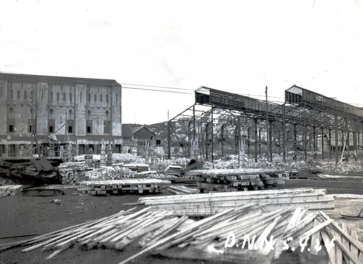 """""""05/04-1924"""" Nitriden. Bygging av stekeribygning for steking av elektrodekull. Jernkonstruksjoner. Omformerstasjonen til venstre. Bærende konstruksjoner for """"høybanen"""", skinneanlegg for intern transport med traller drevet av dieseldrevet lokomotiv. Store stabler med trematerialer."""