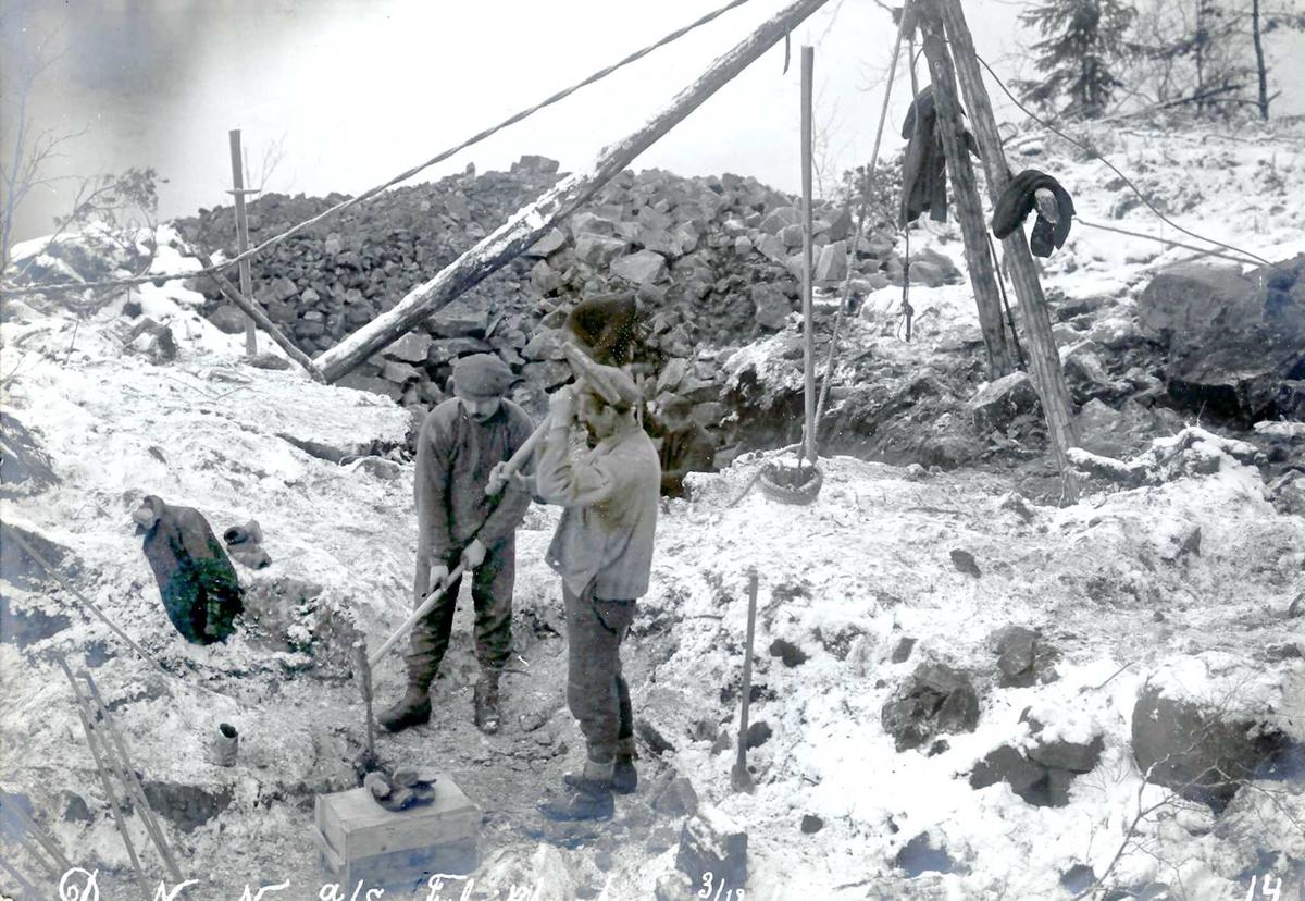 """""""03/12-1912"""" Nitriden. Utsprengning av fabrikktomten. Handboring. To mann slår vekselvis på minebordet. I bakgrunnen en stubbebryter (heisanordning)."""
