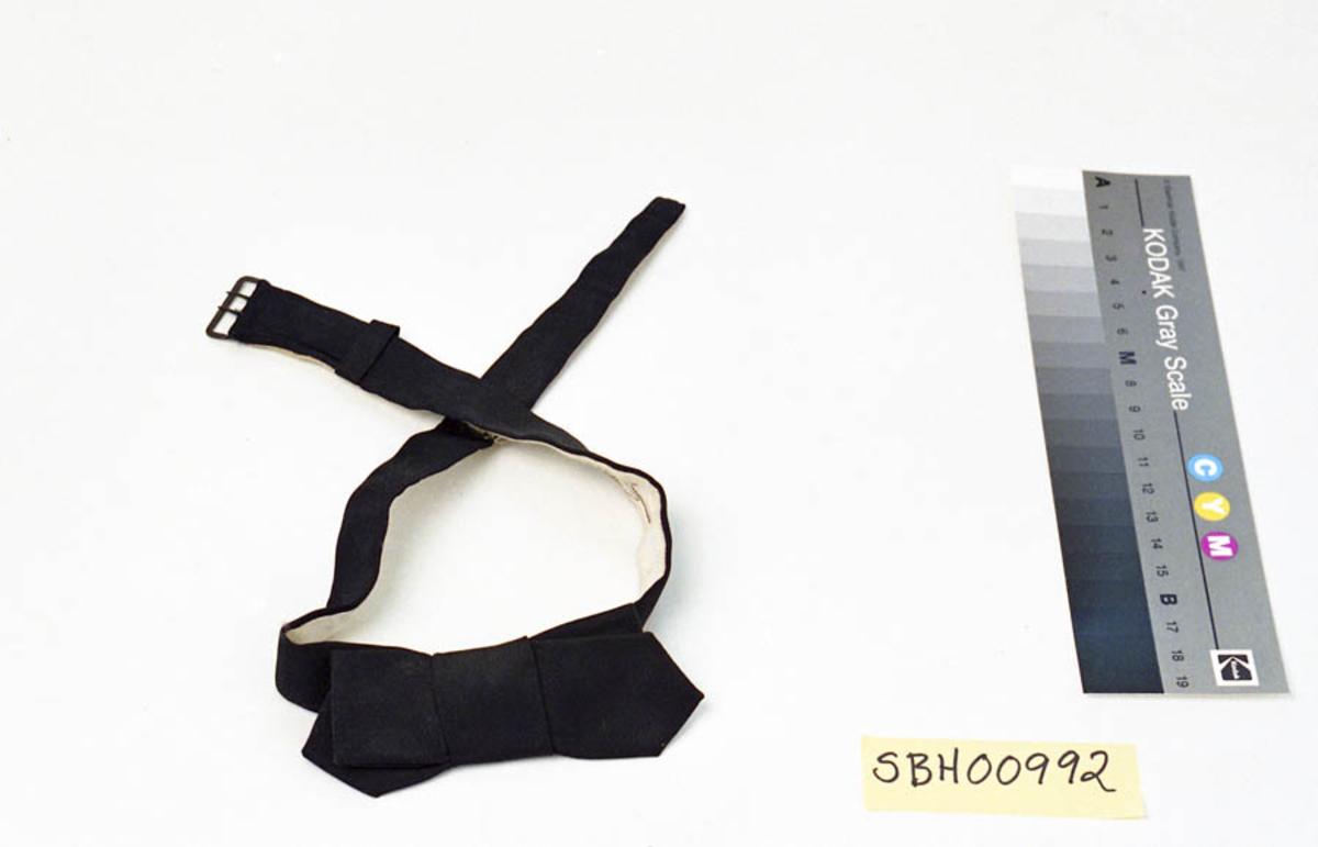"""Form: Sløyfa består av to doble tøystykker, spisse i ene enden, som sitter sammen på en slik måte at det ene synes bakenfor det andre. Og vinkelrett på disse er det sydd på en tøybit, som danner midtpartiet og som klemmer de to litt sammen på midten. Denne sløyfa er festet til en """"lenke"""" i samme stoff, men med bomullsstoff på baksiden, som festes under skjortekragen rundt halsen. Midt på baksiden sitter en blank metallbit som gjør at sløyfa kan hektes på en skjorteknapp. I den ene enden av lenken sitter en liten metallramme med to """"gaffeltinder"""" i, som motsatte enden kan tres gjennom og festes i. Vidden er regulerbar."""