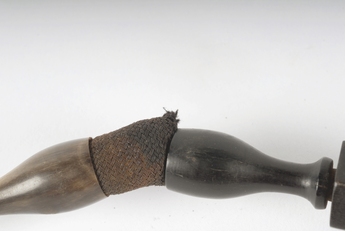Tre deler, øverste del dreiet av horn med 4 vulster. Bevegelig ledd mellom denne og neste del som er av en hard, mørk tresort, dels dreiet, dels sekskantet snitt. Nederste del av løvtre gjenget i enden og skrudd fast i mellomste del. Hører muligens sammen med US 439.