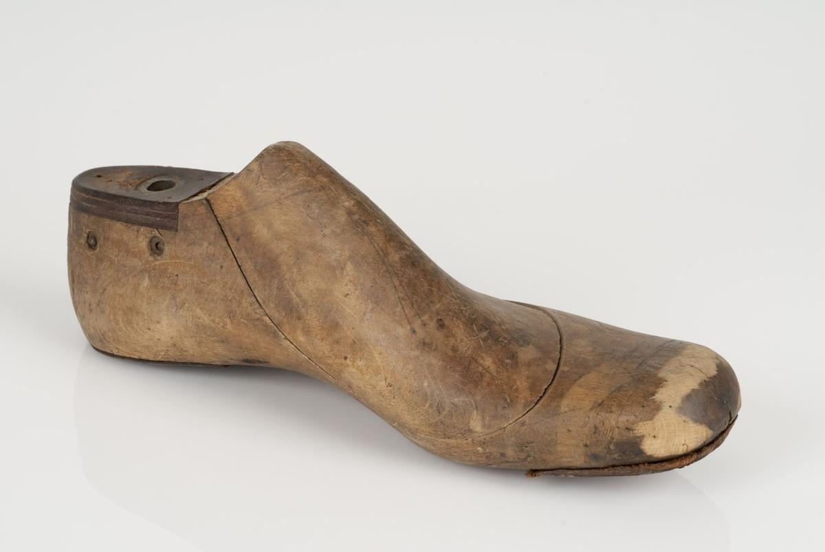 En tremodell i to deler; lest og opplest/overlest (kile). Venstrefot i skostørrelse 44, og 8 cm i vidde. Hælstykket i metall. Lestekam i skinn. Tåspringsåle i skinn.