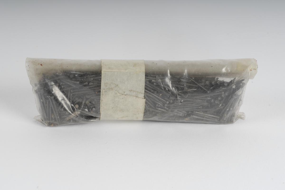 En plastpose som inneholder spiker av stål.
