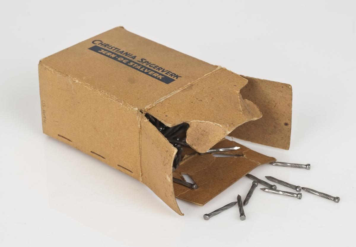 Skruer av stål i en pappeske. Påført tekst på esken. Hvit påklistret merkelapp på undersiden av esken.
