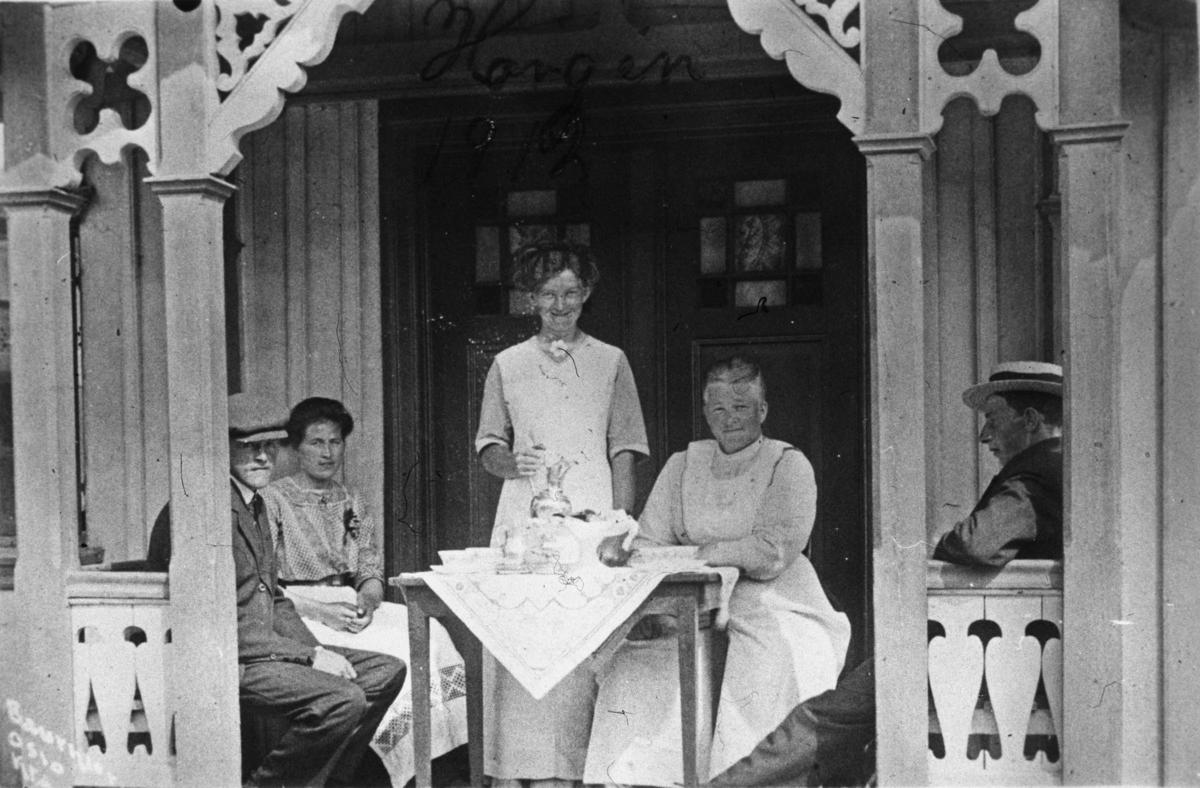 To menn, tre kvinner, kaffebord, veranda