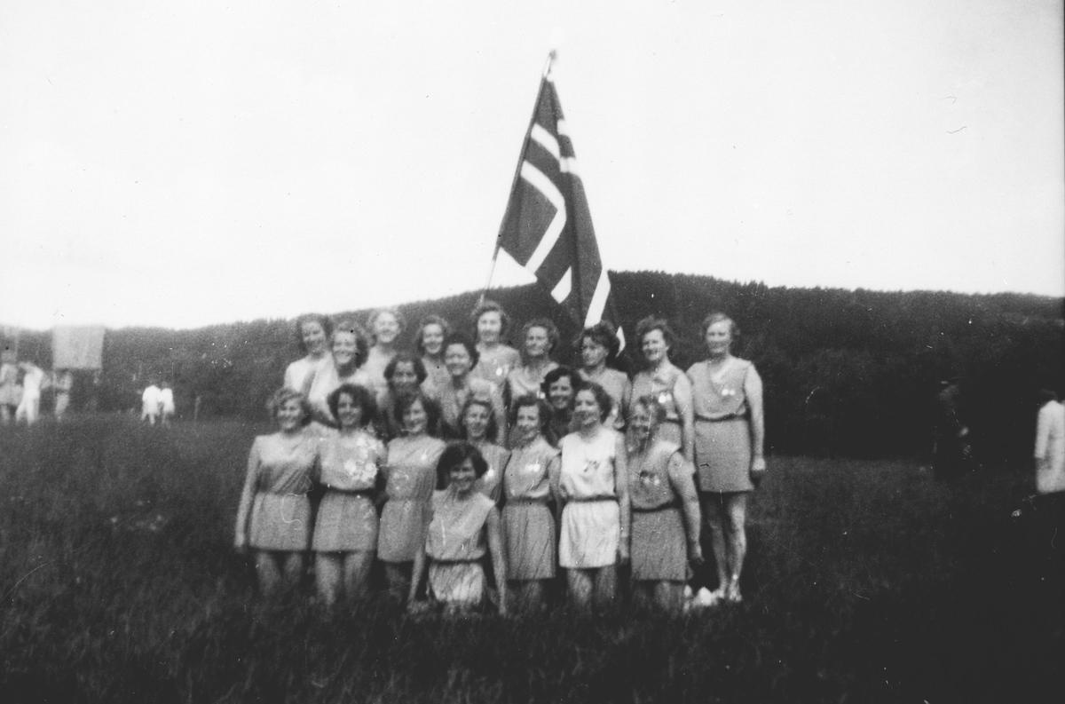 Kvinnelige turnere fra Oppegård oppstilt med norsk flagg.