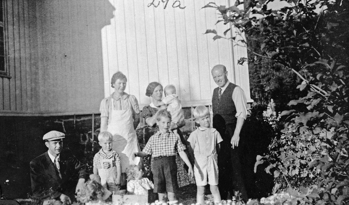 To voksne menn og to kvinner med 5 barn utenfor Fredheim skole.
