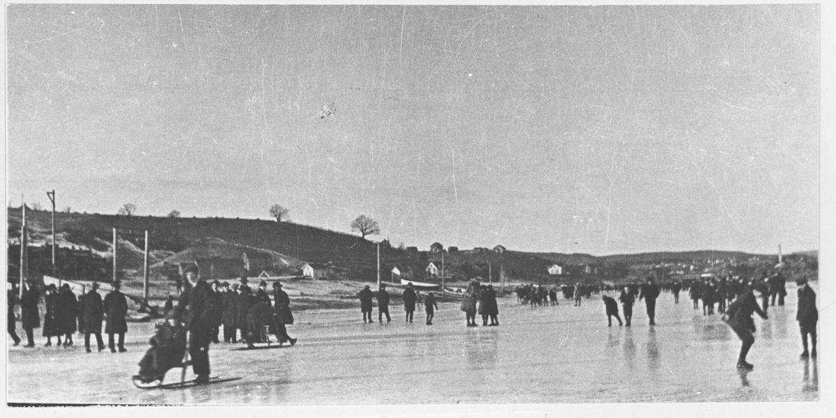 Fra Ekeberg Bruk. Mange personer på isen, på skøter, på spark og på beina. Nesten uten snø.