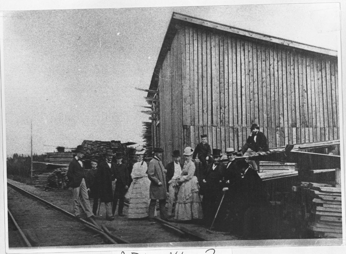 Gruppe personer, jernbanespor, trelastlager