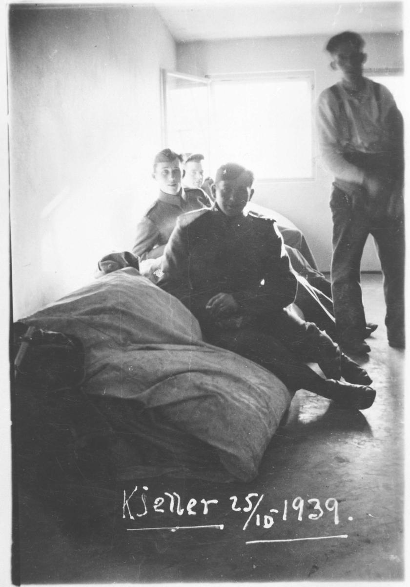 Fire soldater i et rom m/noen halmsekker.