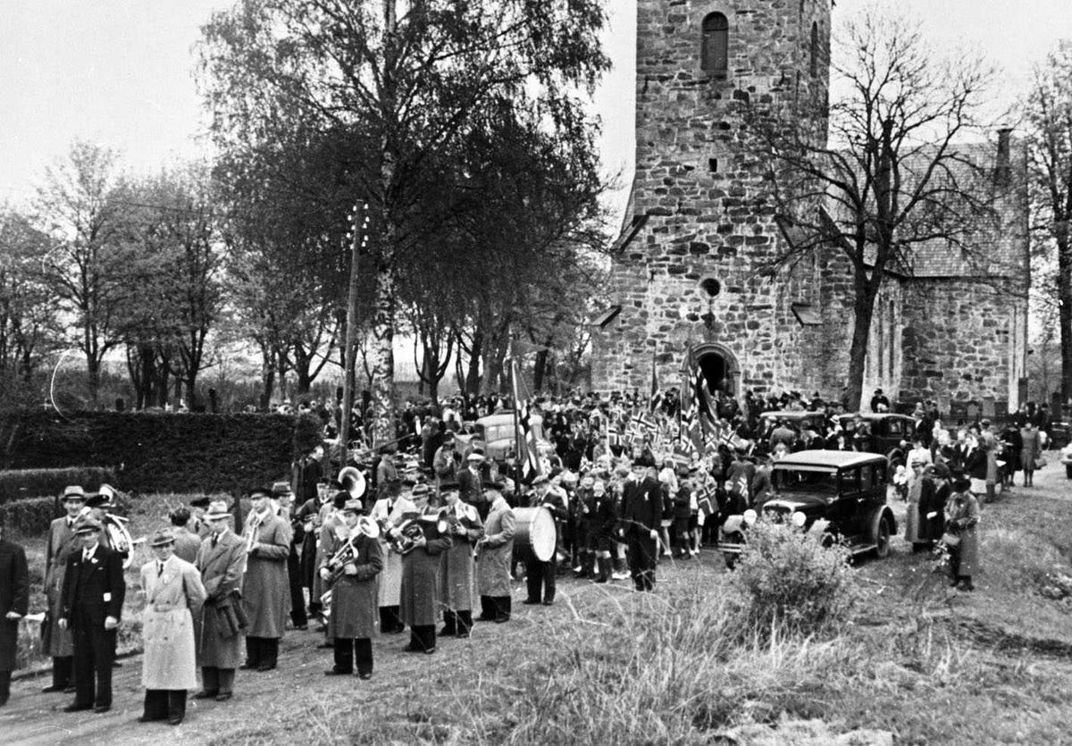 17. mai-tog Skedsmo kirke 1945 Fremst i toget et voksent hornorkester uten uniform. Barn med flagg, biler i grøftekanten langs toget.