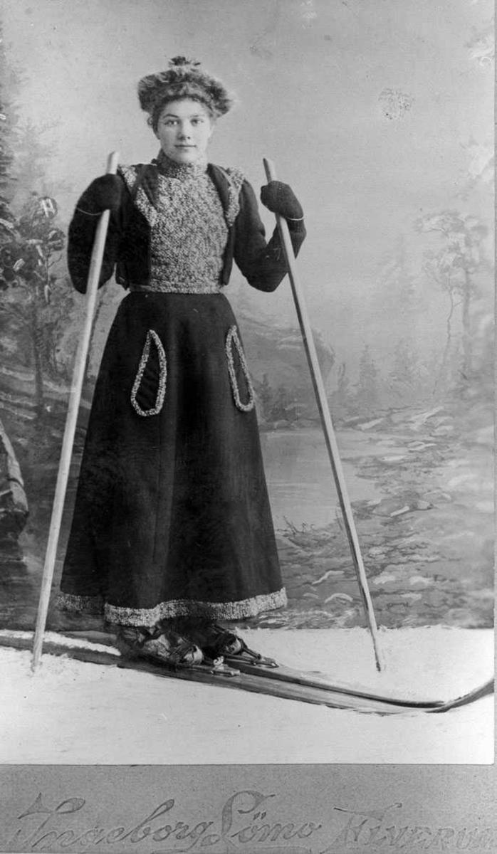 Pent kledd dame på ski, atelierfoto.