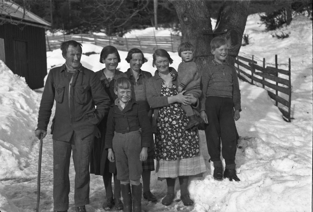 Voksne og barn ute i snøen.