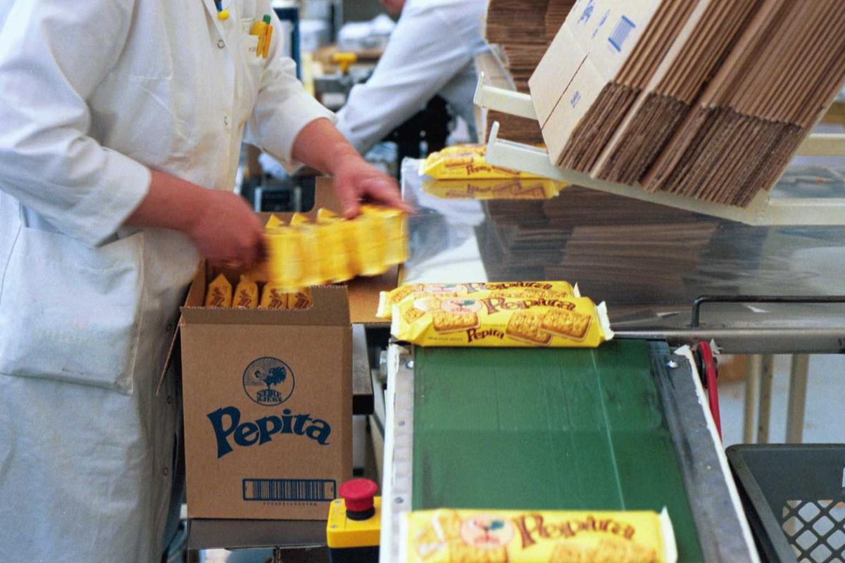 Pepitakjeks, pakkemaskin, arbeider, kvinne, arbeidstøy, arbeidsmiljø, fabrikkmiljø, maskiner, emballasje