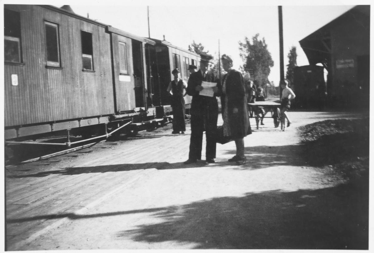 Overkonduktør Henry J. Danielsens i samtale med sin kone foran toget på Sørumsand stasjon.