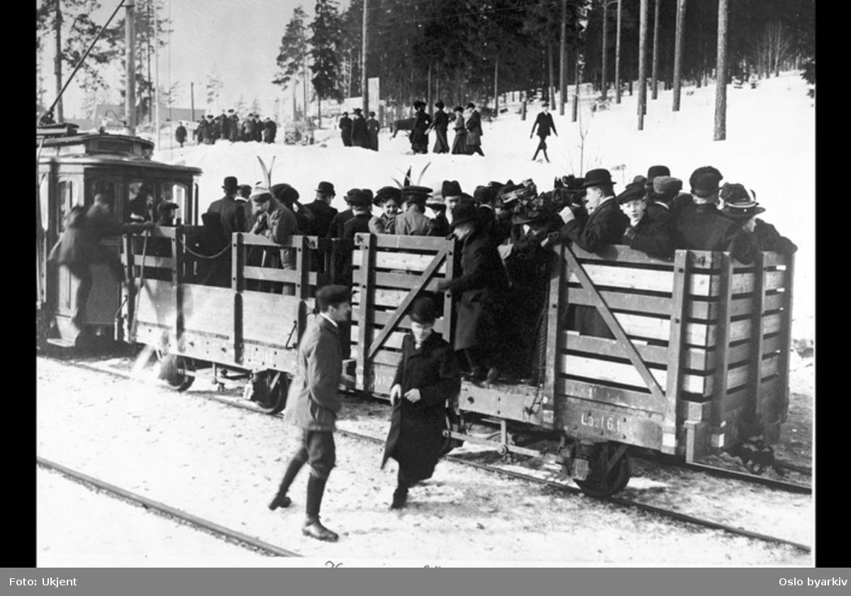 Liten sporvogn med fullstappede åpne tilhengere med passasjerer og ski, snø, vinter. Holmenkollsøndag?