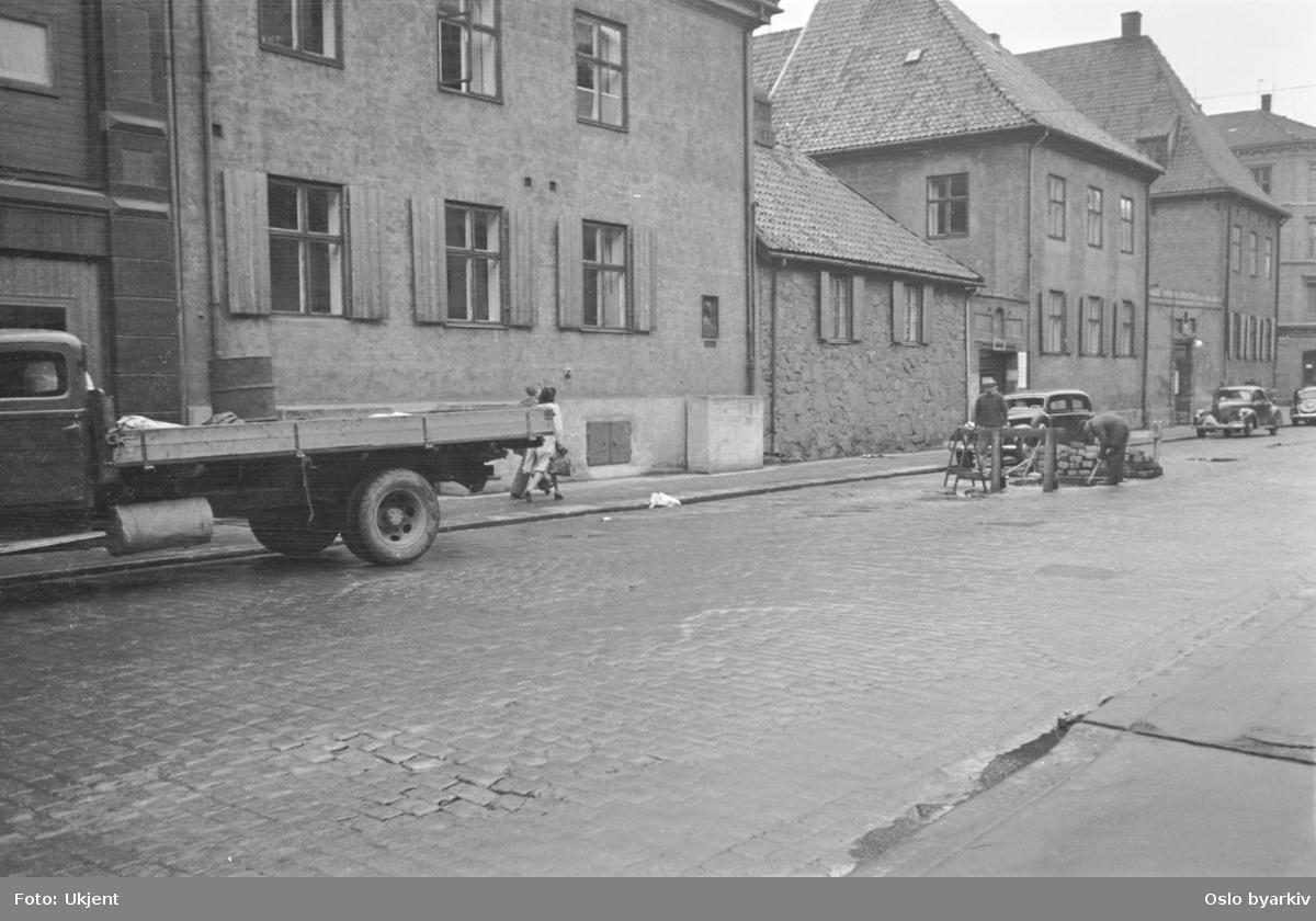 Rådhusgata med Garmanngården i nummer 7 til høyre. Rådhusgata 7B til venstre og 7C (lavbygningen) i midten. Lastebil, veiarveid i gata. Garmanngården var byens andre rådhus (1734-1843). Fredet, en av Oslos eldste bevarte bygninger (eldste bygningsdel fra 1625).