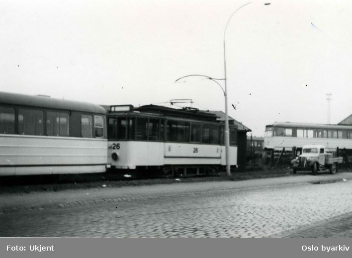 Flere sporvogner tilhørende Trondheim Sporvei. Lastebil parkert like ved. Bilde tatt ved sidesporet ved jernbanen. Bak lastebilen sees gamle vogn nr 46 som skal benyttes til å trekke opp motorvognen som står opplastet på jernbanevogn i bakgrunnen.
