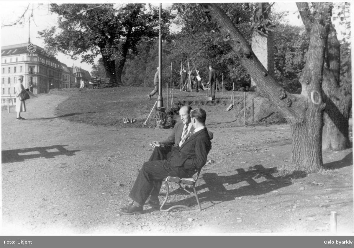 To herrer sittende på en benk ved Abelhaugen. Arbeidere i gang med oppmåling av gangvei over haugen ved Abelmonumentet. Kvinne iakttar arbeidet. Glitnegården i bakgrunnen. Bildet tatt 1949 - 50.
