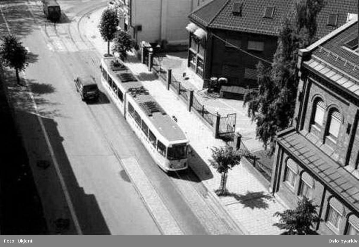 """Oslo Sporveier. Trikk motorvogn type SL79 ved Schous bryggeri nederst i Trondheimsveien. Sannsyligvis fra 1990-tallet, basert på kommentar fra bruker: Det er et helt vindu bakerst (ikke enkeldør), noe som først kom på SL-79 II-serien (nr. 126-140), med dobbel bakdør, levert mot slutten av 80-tallet (1989/90?). Gråtonene og lyktene underbygger også dette, da det ser ut som det """"nye"""" lyseblå designet og moderne lykter."""