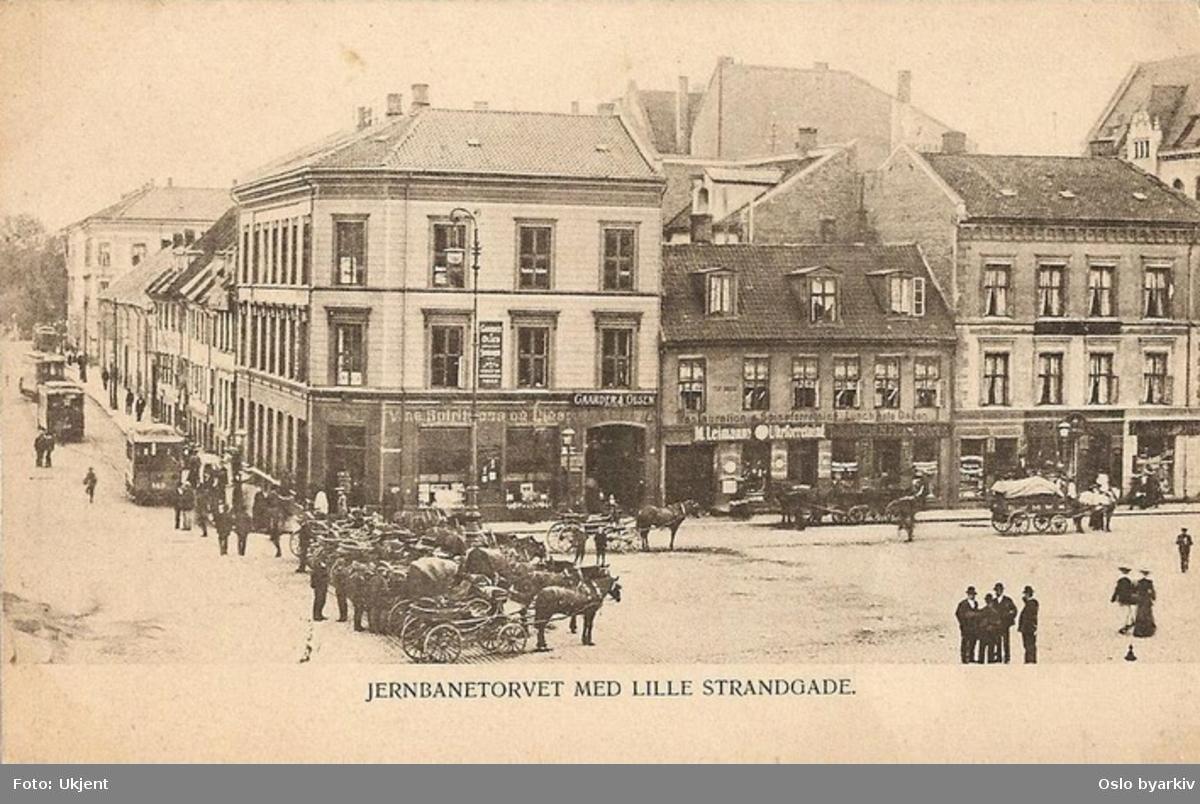 Jernbanetorget ved Lille Strandgate (Strandgata fra 1934) til venstre. Hestedrosjer oppstilt, hestetransport, butikker, Blåtrikker. Gamle bygårder med butikker der Amerikalinjens bygning står idag. Postkort.