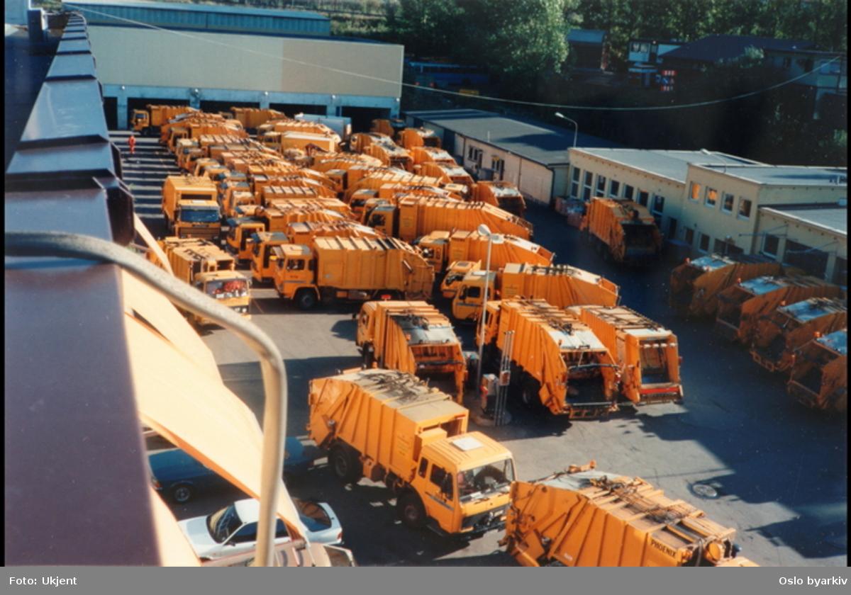 Oransje søppelbiler på parkeringsplass.