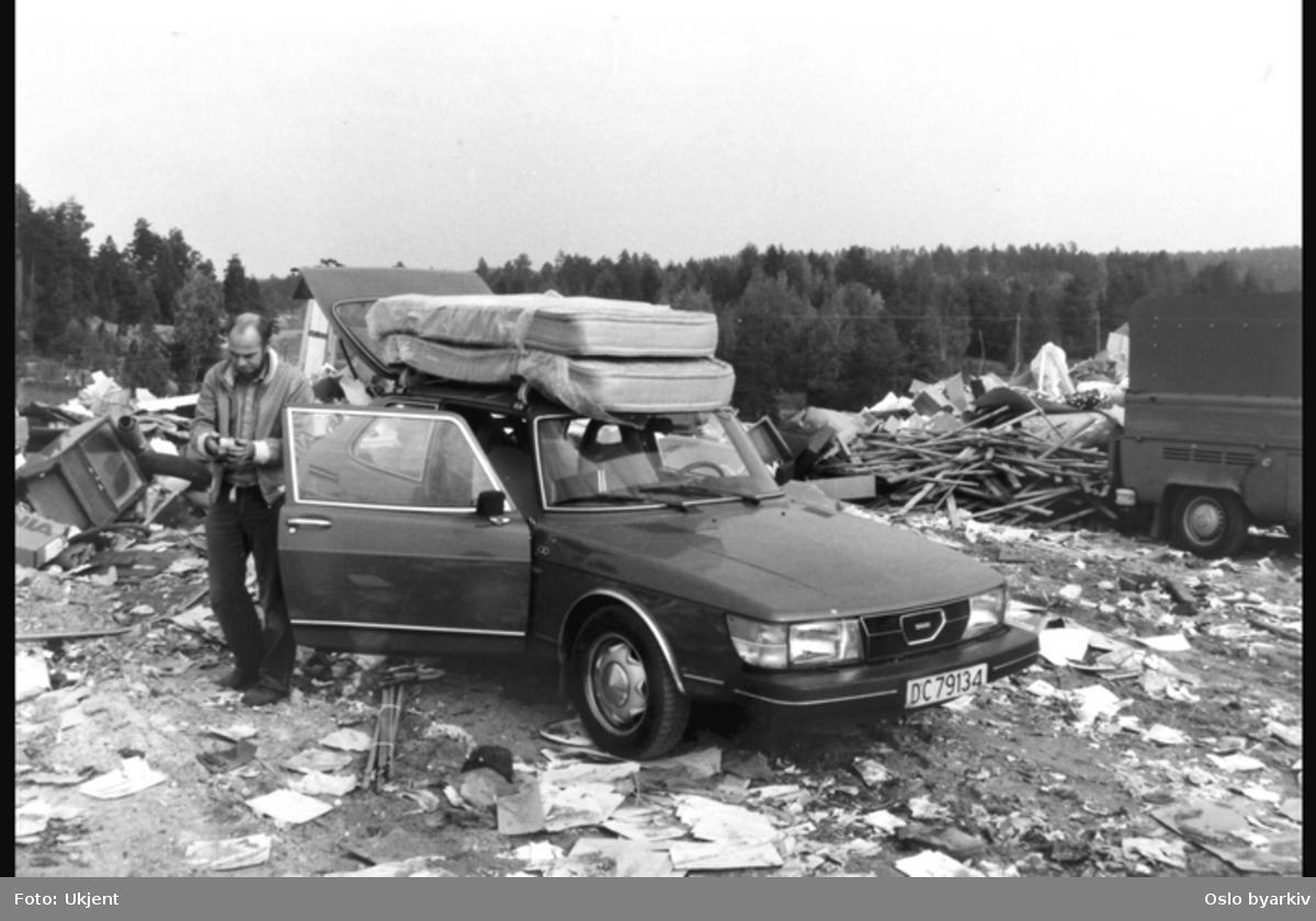 Mann ved overlesset bil (Saab) på søppelfylling.