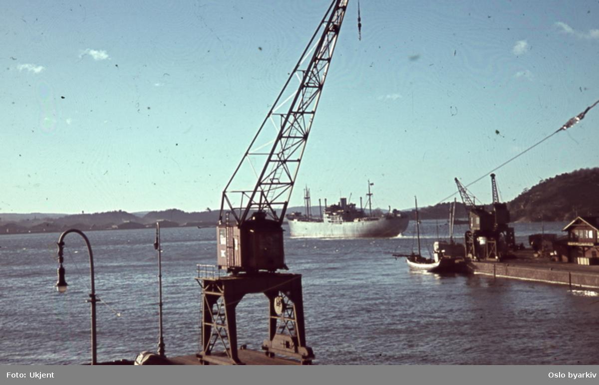 Havnekran og lastebåt utenfor Vippetangen eller Akershuskaia. Sannsynligvis fotografert fra båt ved kai av tysk soldat under krigen.