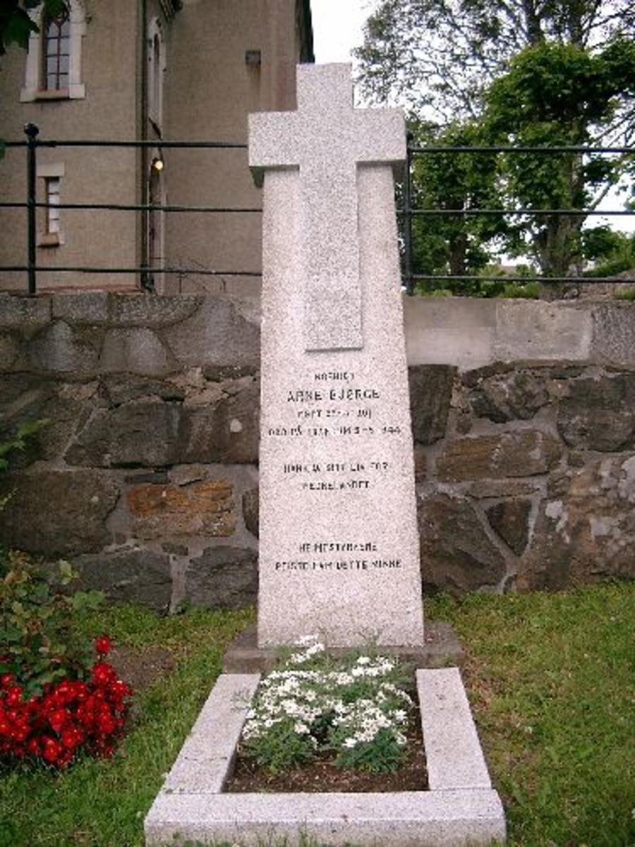 Bauta i granitt, med kors i øverste del av steinen.