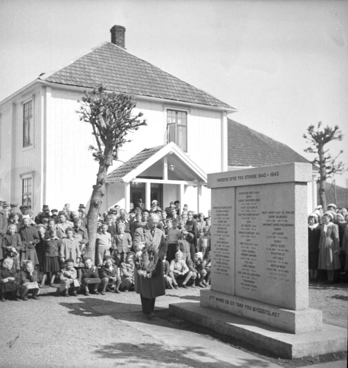 17 MAI, MANN LEGGER NED KRANS VED BAUTA FOR KRIGENS OFRE, SENERE FLYTTET TIL SOLE. BEDEHUSET I BAKGR. SE ÅRBOKA 2006 S. 142.  Sogneprest, senere prost Sigvald Krohn legger ned krans ved minnebautaen over krigens ofre 8. mai 1953.