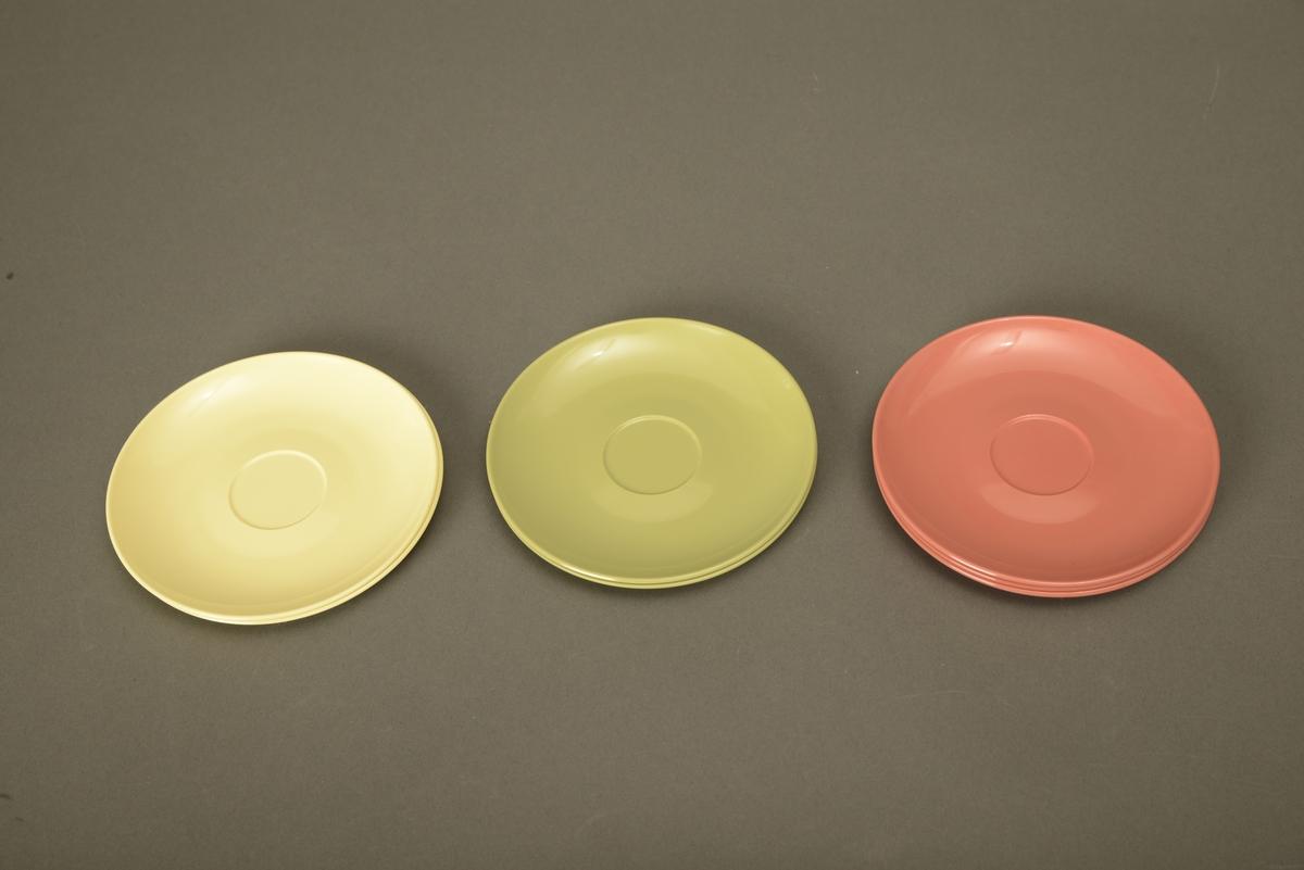 Sju tefat laget av plast med en blank overflate. To gule-, tre rosa-, og to grønne tefat.Tefatene er del av innholdet i en campingkoffert. Bortsett fra fargeforskjellen er de identiske.