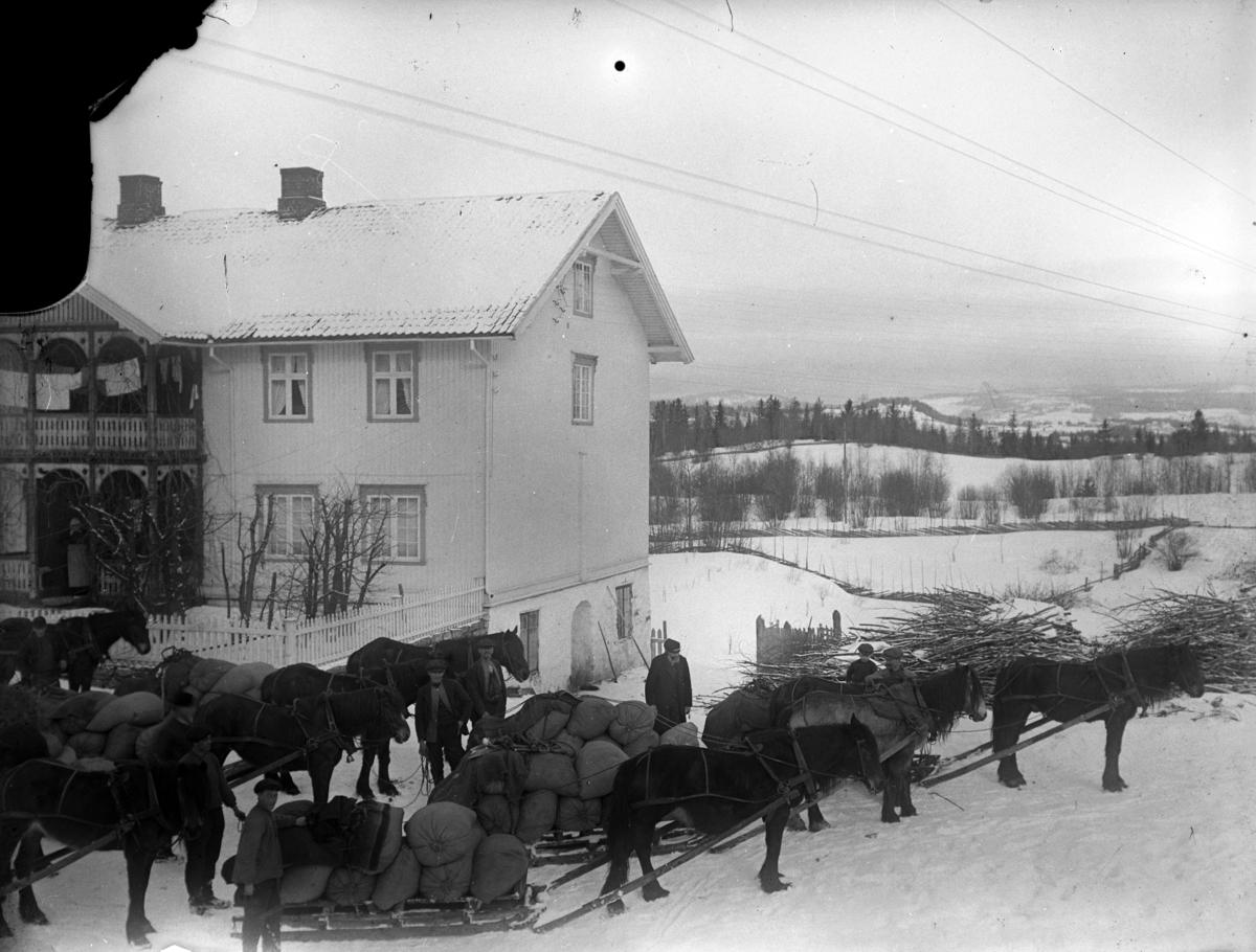 Gårdstun, ukjent. Hester med kløvsaler og hester med store striesekker på sleden. Vinter.
