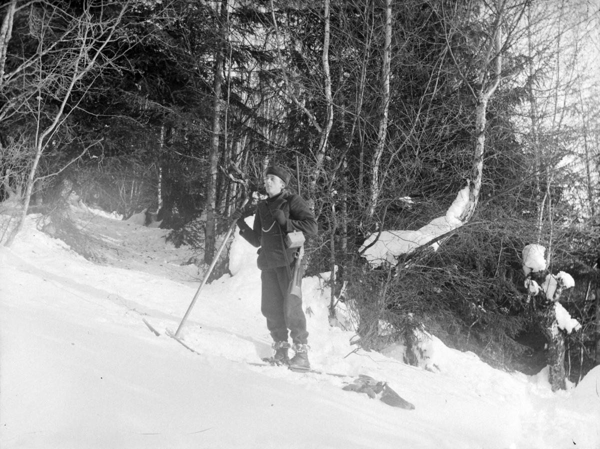 Eksteriør, skog, vinter. Ukjent jeger med gevær på ski.