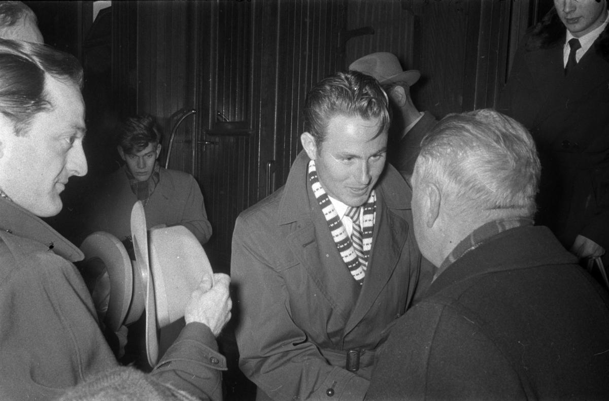 Egil Danielsen kommer hjem til Hamar etter å ha vunnet Olympisk gullmedalje i Spyd i Melbourne 1956. Hamar Jernbanestasjon. Han blir ønsket velkommen hjem av rådmann Sigurd Pedersen.