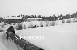 """Transport av diger furustokk over snødekte jorder mot garden Tollås, den gang gardsnr. 1 og bruksnr. 1 i Bolsøy kommune, seinere gardsnummer 1964 i Molde kommune.  I forgrunnen til venstre ser vi Nils Tolaas (1893-1973), som kjørte en ualminnelig lang og grov furustokk over et snødekt jorde i retning mot garden.  Stokken trekkes av hest med en todelt slede (bukk og geit, i Romsdalen """"framslede og bakslede"""") med krysslagt trosse mellom.  Den krysslagte kjettingen fikk baksleden til å gå i sporene etter framsleden.  Om baksleden skar ut, tok kjørekaren et godt tak i kjettingen mens hesten drog, inntil sleden var på rett spor igjen.  På framsleden var det en jernkam med 2-3 centimeter lange tagger på """"dragåsen"""".  I dette distriktet ble stokkene alltid """"fastjørra"""" (surra til sleden) med """"rossmålreip - lærreip av kvalrosskinn som var innsmurt med ei blanding av kokt dyrefett og litt tjære for å få nødvendig smidighet.  Tømmeret kjøres på en smal veg som er brøytet med hest og treplog."""
