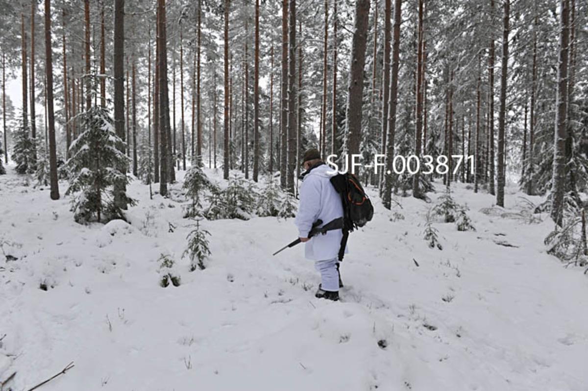 Fra anleggsarbeidet i forbindelse med bygginga av Geithus Bruk på Modum i Buskerud i 1965.  Fotografiet er tatt i mars måned, fra en snødekt og brøytet veg, omgitt av bjørke- og furuskog.  Et stykke framme i vegen ser vi en mannsskikkelse.  Enda lengre framme ser vi røyken fra en eksplosjon, antakelig sprenging med sikte på å planere arealet for bedriften eller kranbanen som skulle bringe tømmer til anlegget.  Geithus Bruk var en bedrift som kjøpte tømmer for barking og opphogging til flis, som ble sendt videre til Skotselv Cellulosefabrik, hvor flisa ble kokt til masse.