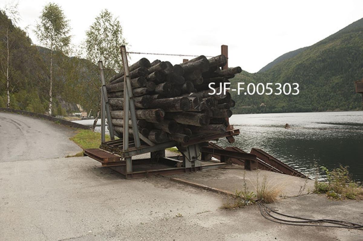"""Utislagsplass med tømmermålingsfasiliteter ved Dalen i Tokke i Telemark.  Anlegget ligger like øst for tettstedet, ved den såkalte Lasteinsvingen, der det omkring 1960 ble bygd en veg langs stranda mot kraftstasjonen Tokke 1.  Ved denne vegen ble det tippet steinmasser med sikte på å etablere en utislagsplass for lastebiltransportert tømmer.  Tømmeret ble lenge tippet direkte fra lastebilene, som da sto ytterst på fyllinga.  Dette var en rimelig avlastingsmetode for Skiensvassdragets Fellesfløtningsforening, men for transportørene representerte den en betydelig slitasjefaktor på lastebilene.  I tillegg så man tydelige tegn til undervasking i skråningen fra tippstedet ned mot innsjøen.  Ettersom utislagsplassen var ei fylling i et terreng som skrådde bratt ned mot cirka 40 meters djup, ble tipping av tømmerlass fra ytterkanten av denne fyllinga etter hvert betraktet som risikofylt.  I 1987 gikk derfor Tokkekraftverkene med på å plassere ei """"vogge"""" der lastebilene tidligere hadde stått når lassene ble tippet.  Dermed kunne bilene stå trygt innenfor, mens sjåførene ved hjelp av griplastekranene på kjøretøyene flyttet tømmeret fra bilene over i vogga.  Når dette var gjort ble det slått en vaier rundt tømmeret i vogga.  Så ble stakene på sida mot vannet felt ned, før den indre delen av vogga ble hevet ved hjelp av en hydraulisk innretning.  Dette førte til at tømmerbuntene («klubbene») skled på stålskinner ned den nedenforliggende skråningen og ut i vatnet med et stort plask.  Utislagsplassanlegget omfattet også ei inspeksjonsrampe for lassmåling av tømmer og ei kontorbrakke for tømmermålere, som ikke er med på dette fotografiet.   På Bandak, like utenfor utislagsstedet, ble tømmerbuntene bundet sammen i slep, som ble trukket over Vestvannene (Bandak, Kviteseidvatn og Flåvatn) med slepebåt.  Fram til cirka 1980 ble tømmeret fløtet videre ned gjennom sluseanleggene Bandak-Norsjøkanelen, over Norsjø, og via Løveid sluser til Skien.  Fra da og fram til tidlig på 2000-tallet"""